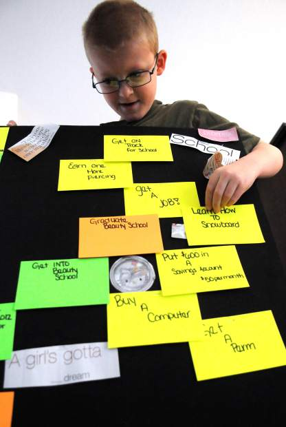 JOSHUA POLSON/jpolson@greeleytribune.com Isaac Johnson, 9, examines a board that his sister Alexa had made for her goals Thursday morning at his home in Loveland. The Johnson family kept the board after Alexa died in honor of her and to remember her aspirations.