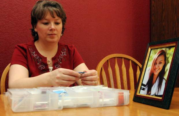 JOSHUA POLSON/jpolson@greeleytribune.com Jona Johnson, sifts through a small case of the Alexa's Hugs ribbons she designed Thursday while at her home in Loveland. The ribbons have been shipped to 10 different states. Johnson has put together nearly 700 of the ribbons within the past few months.