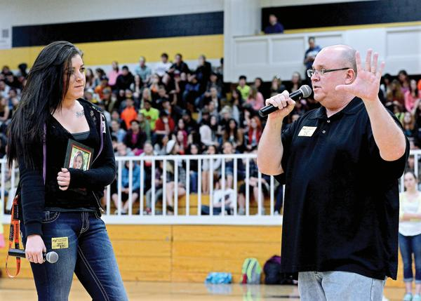 Tad Johnson, right, speaks to Thompson Valley High School students Friday about a seat belt challenge among area high schools. His daughter, Alexa Johnson, was killed in a car crash last year and was not wearing her seat belt. Kaley Germer, left, holds a photo of Alexa while waiting to speak about losing her best friend. (Jenny Sparks / Loveland Reporter-Herald)