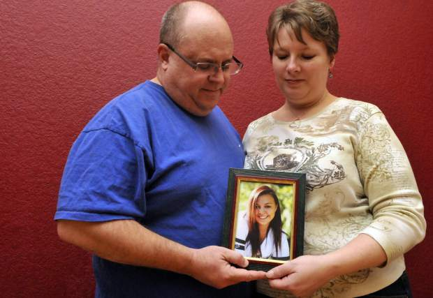 Tad and Jona Johnson hold a photo of their daughter, Alexa, on Thursday at their home in Loveland.